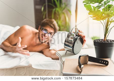 Furious male is lying on bed and watching time at alarm-clock. smartwatch near silver clock