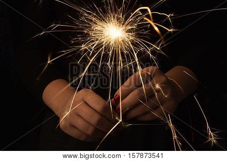 New year party burning sparkler closeup in female hands on black background. Woman holds glowing holiday sparkling hand fireworks, shining fire flame. Christmas light.