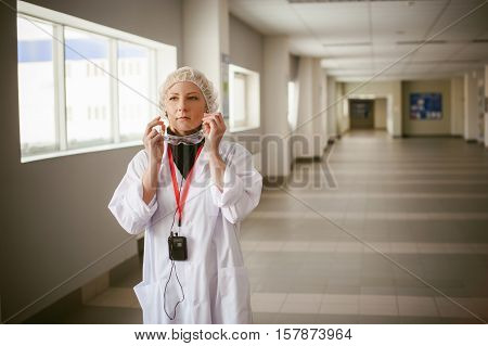 Woman In Overalls. Employee Wears Protective Glasses, Wearing A White Robe And A Protective Cap, Ear
