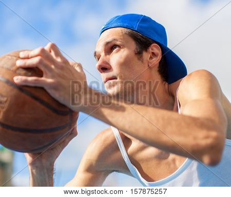 Young guy is playing basketball. He is preparing to throw the ball in the basket. Focus on the basket