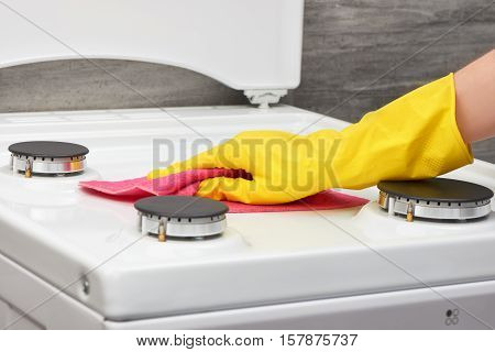 Hand In Yellow Glove Cleaning White Stove With Pink Rag