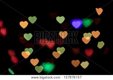 Bokeh vague colorful heart shaped small scattered celebration lights on black background