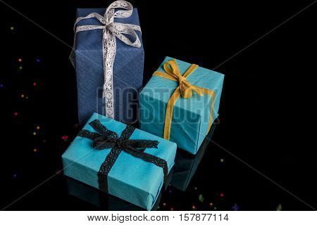 Three presents of different sizes wrapped in blue and turquoise textured paper tied with lace and velvet ribbons on black from high angle with colorful lights