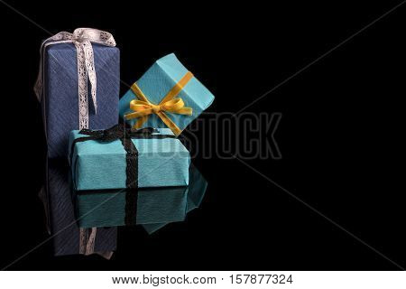 Three presents of different sizes wrapped in blue and turquoise textured paper tied with lace and velvet ribbons on black from side with reflection copy space