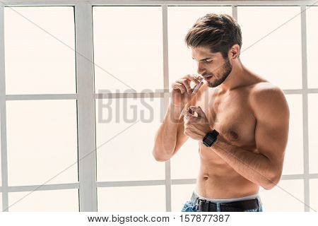 Attractive young man is lighting up a cigarette indoors. He is standing near window with naked muscular torso