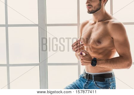 Sexy guy is smoking near window at home. He is holding cigarette and lighter. Smart watch on his arm