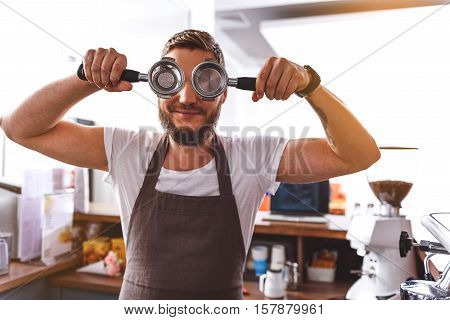 funny barman holding a portafilters near his eyes against kitchen background