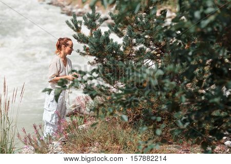 The girl in the mountains near the river collects wild berries.