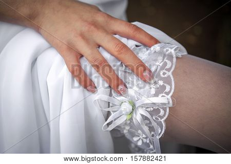 Garter from the bride. The bride's hand touches the lace garter on her leg. Wedding apparel dress for the bride. The wedding attire. Clothing for the newlyweds.