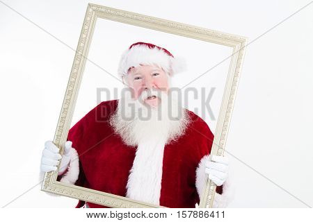 Santa Claus framed in a picture frame that he is holding