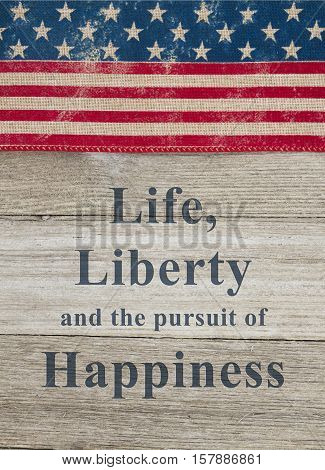 USA patriotic message USA patriotic old flag on a weathered wood background with text Life Liberty and the pursuit of Happiness