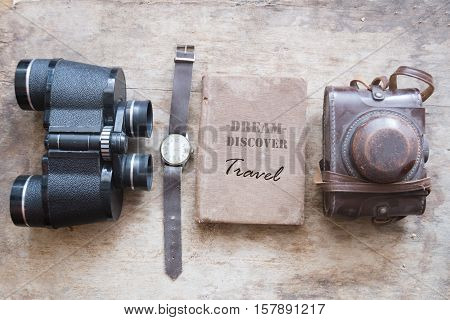 Dream Discover Travel - inscription on an old book and binoculars, watch, retro camera on vintage table.