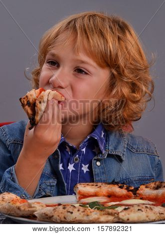 Happy blonde kid eating pizza portrait.