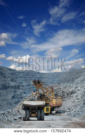 Heavy mining dump trucks are being loaded with iron ore on the opencast mining on a sunny day poster