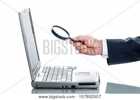 Closeup of a Businessman Looking at Laptop Through Magnifying Glass