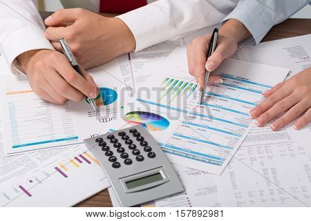 Closeup of Business People Analyzing Financial Figures with Calculator