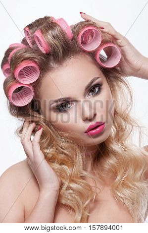 Beauty woman with beautiful makeup and hair curlers in her hair. Blond hair wavy hair clear skin beautiful face. Portrait shot in studio on white background.