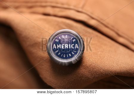 Button with text MADE IN AMERICA ORIGINAL on garment, closeup. Manufacturing quality concept.