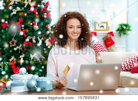 Young woman shopping online with credit card at home for Christmas. Snowy effect. Christmas shopping concept.