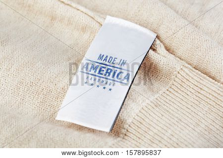 Garment label with text MADE IN AMERICA HANDMADE, closeup. Manufacturing quality concept.