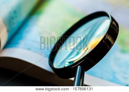 Closeup of a Magnifying Glass on an Atlas