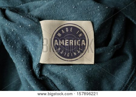 Garment label with text MADE IN AMERICA ORIGINAL, closeup. Manufacturing quality concept.