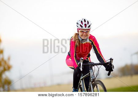 Happy sporty woman in sports protective clothing riding bicycle