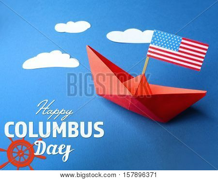 Text HAPPY COLUMBUS DAY with paper boat and USA flag on blue background. National holiday concept.
