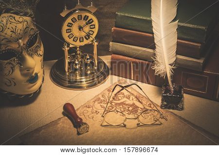 Old glasses on scroll with books old clock feather in inkstand and venezian mask. Vintage toned photo.