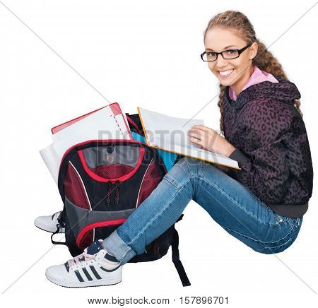 Friendly Young Girl with Rucksack and Book Sitting on Ground - Isolated