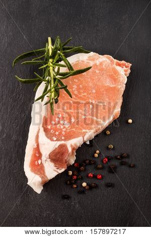 raw pork loin steak with rosemary peppercorn and coarse salt on slate