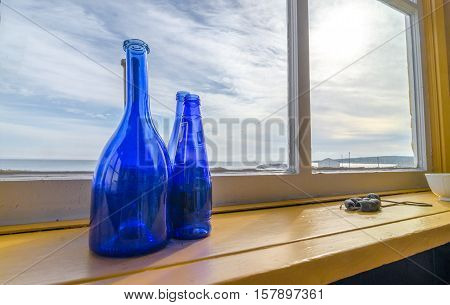 Blue bottles in a window beside the sea, Newfoundland Canada.  Wide Angle view, Blue glass bottles decorate a shelf at a window with a view to the Atlantic in Grand Bank Newfoundland.