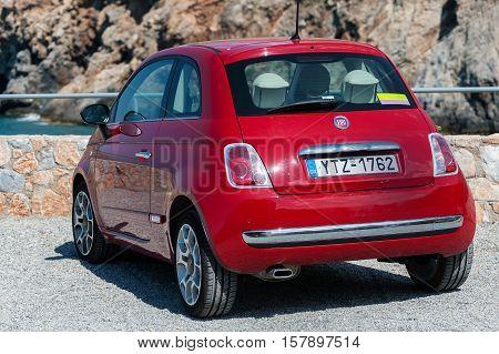 CHORA SFAKION, CRETE, GREECE - JULY 2016: Red Fiat 500 stays parked at street of Chora Sfakion town on Crete island