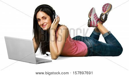 Young woman lying down in front of her laptop with headphones on