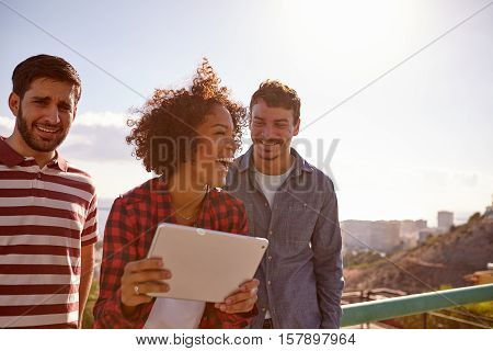 Three Laughing Millennials With A Tablet
