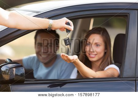 Portrait of a Couple in a Car with Woman Receiving Car Key from Salesman