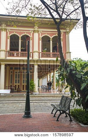 Metal bench with old colonial houses in the background, in a national park in Guayaquil city, Ecuador.