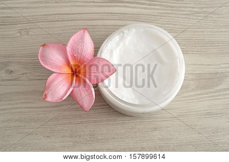 Body lotion in a container with a pink frangipani flower