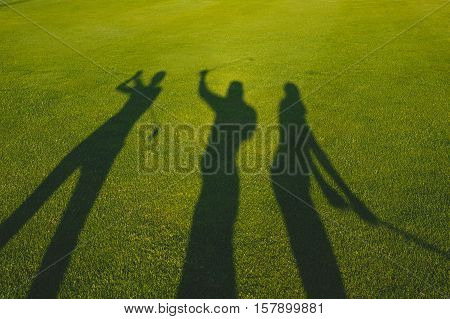 Three golfers with open hands silhouette on grass