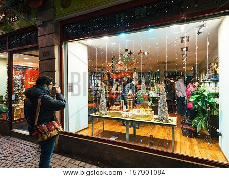 STRASBOURG FRANCE - DEC 06 2016: Man drinking hot cup of tea in front of Tea Shop admiring the people buying tea and the Christmas decorations of the window shopping atmosphere drink
