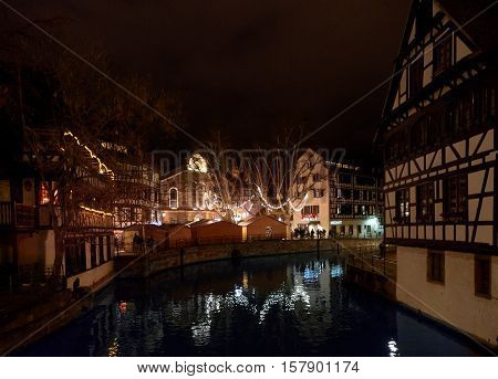 STRASBOURG FRANCE - DEC 6 2016: Christmas market in Place Benjamin Zix with its reflection in the Ill river at dusk with Christmas stalls and people shopping drinking mulled wine