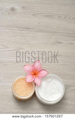Body lotion and bath salt displayed with a frangipani flower