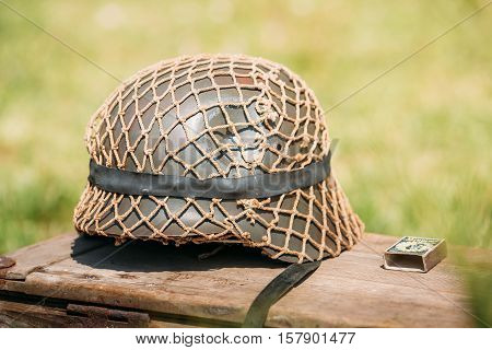 Close The Metal Helmet Of Infantry Soldier Of Wehrmacht, Armed Forces Of Nazi Germany During World War II, Lying On The Old Wooden Box On The Green Grass Background.