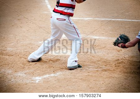 Close up of lower part of baseball boy standing at home plate to swing at the pitch.