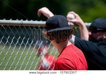 Teen boy and middle-aged father leaning on fence.