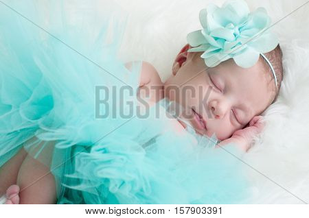 Precious baby girl sleeping in teal outfit laying on white fur.