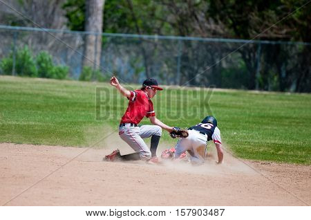 Baseball shortstop tagging out a player sliding at second base.