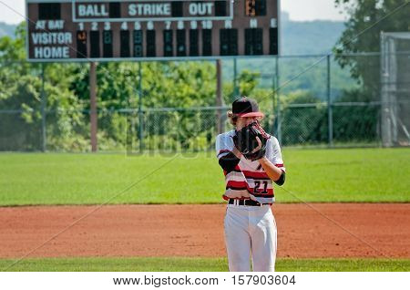 American teenage baseball pitcher being focused on the mound during the game with his face in his glove.