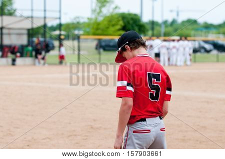 Young baseball boy on the field during a game.