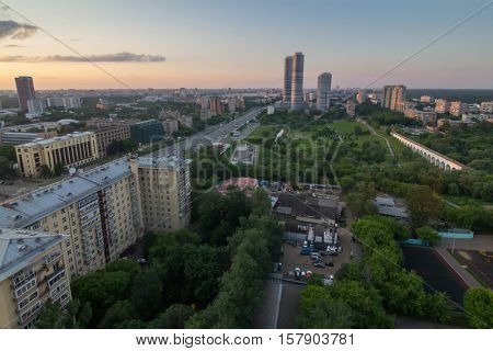 Road, green park and skyscrapers in Moscow, Russia at summer evening